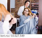 Купить «Woman points to master in hairdress salon right hair length for haircut», фото № 33027549, снято 7 марта 2017 г. (c) Яков Филимонов / Фотобанк Лори