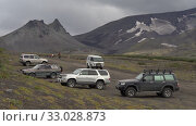 Parking extreme off-road expedition cars, SUV travelers at foot of volcano - popular travel destinations for climbing, hiking, observing wildlife. Kamchatka Peninsula (2019 год). Редакционное видео, видеограф А. А. Пирагис / Фотобанк Лори