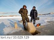 Fitter with steel tongs pulls out ice block (2020 год). Редакционное фото, фотограф Андрей Кузнецов / Фотобанк Лори