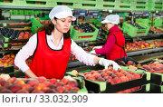 Купить «Female employee sorting fresh ripe peaches», фото № 33032909, снято 21 февраля 2020 г. (c) Яков Филимонов / Фотобанк Лори
