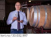 Купить «Winemaker inviting to wine degustation», фото № 33032997, снято 22 января 2018 г. (c) Яков Филимонов / Фотобанк Лори