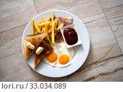 Купить «Fried eggs with toast and french fries for breakfast», фото № 33034089, снято 6 июля 2019 г. (c) Володина Ольга / Фотобанк Лори