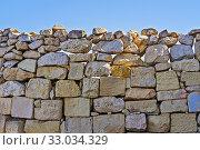 Limestone wall of brickwork with cracked boulders against blue sky. Стоковое фото, фотограф Kira_Yan / Фотобанк Лори