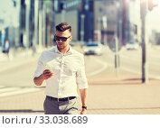 Купить «man in sunglasses with smartphone walking at city», фото № 33038689, снято 21 августа 2016 г. (c) Syda Productions / Фотобанк Лори