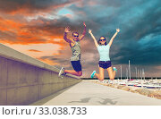 Купить «happy couple in sports clothes jumping on pier», фото № 33038733, снято 1 августа 2018 г. (c) Syda Productions / Фотобанк Лори