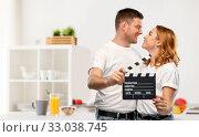 Купить «happy couple in white t-shirts with clapperboard», фото № 33038745, снято 6 октября 2019 г. (c) Syda Productions / Фотобанк Лори