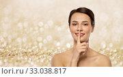 Купить «beautiful young woman holding finger on lips», фото № 33038817, снято 30 ноября 2019 г. (c) Syda Productions / Фотобанк Лори
