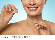 Купить «smiling woman with dental floss cleaning teeth», фото № 33038837, снято 30 ноября 2019 г. (c) Syda Productions / Фотобанк Лори