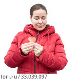Купить «Young woman in red jacket holding paper heart shape in hands, Caucasian female with closed eyes, isolated on white background», фото № 33039097, снято 6 января 2020 г. (c) Кекяляйнен Андрей / Фотобанк Лори