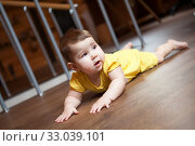Купить «Seven month old baby trying to crawl on hardwood floor in domestic room», фото № 33039101, снято 7 января 2020 г. (c) Кекяляйнен Андрей / Фотобанк Лори