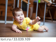 Cute little baby girl lying on hardwood and smiling. Child crawling over wooden parquet with happy face. Стоковое фото, фотограф Кекяляйнен Андрей / Фотобанк Лори