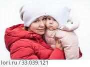 Купить «Cute baby in mothers arms outdoors portrait. Happy mom and baby in winter clothing, isolated on white background», фото № 33039121, снято 6 января 2020 г. (c) Кекяляйнен Андрей / Фотобанк Лори