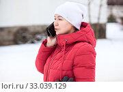 Woman dressed winter clothing calls by cellphone on cold street, red jacket, white hat. Стоковое фото, фотограф Кекяляйнен Андрей / Фотобанк Лори