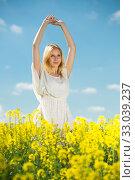 Купить «Young woman in yellow oilseed rape field stretch oneself outdoor», фото № 33039237, снято 8 апреля 2019 г. (c) Яков Филимонов / Фотобанк Лори
