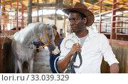 Купить «Man in working clothes posing at stable», фото № 33039329, снято 2 октября 2018 г. (c) Яков Филимонов / Фотобанк Лори