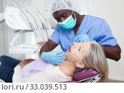 Купить «Dentist is treating female patient which is sitting in dental chair in clinic», фото № 33039513, снято 18 марта 2019 г. (c) Яков Филимонов / Фотобанк Лори