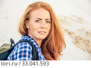 Купить «Portrait of stylish hipster young girl with red hair and freckles in a checkered shirt on slope dune. With backpack. Travel, hiking and active lifestyle concept.», фото № 33041593, снято 4 апреля 2020 г. (c) easy Fotostock / Фотобанк Лори
