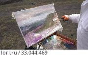 Купить «Young creative artist painting oil paints on canvas autumn mountains landscape», видеоролик № 33044469, снято 30 августа 2019 г. (c) А. А. Пирагис / Фотобанк Лори
