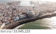 Купить «Aerial view of old town Cadiz with port and buildings at seashore, Spain», видеоролик № 33045233, снято 19 апреля 2019 г. (c) Яков Филимонов / Фотобанк Лори