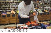 Купить «African American man shopping in organic food store, choosing fresh vegetables», видеоролик № 33045413, снято 9 апреля 2020 г. (c) Яков Филимонов / Фотобанк Лори