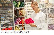 Купить «Smiling young saleswoman offering colorful ribbons and braid for sewing in haberdasher shop», видеоролик № 33045429, снято 4 августа 2020 г. (c) Яков Филимонов / Фотобанк Лори