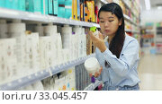 Купить «Asian female customer choosing hair dye in hair care products shop», видеоролик № 33045457, снято 4 августа 2020 г. (c) Яков Филимонов / Фотобанк Лори