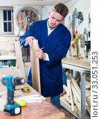Guy carpenter adjusting chipboard at workshop. Стоковое фото, фотограф Яков Филимонов / Фотобанк Лори