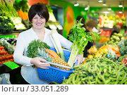 Купить «Middle aged woman with basket choosing vegetables», фото № 33051289, снято 10 марта 2017 г. (c) Яков Филимонов / Фотобанк Лори