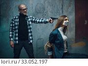 Купить «Maniac kidnapper puts a gun to his victim's head», фото № 33052197, снято 13 ноября 2019 г. (c) Tryapitsyn Sergiy / Фотобанк Лори
