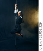 Купить «Sexy nun in cassock dances on pole like a stripper», фото № 33052329, снято 14 ноября 2019 г. (c) Tryapitsyn Sergiy / Фотобанк Лори