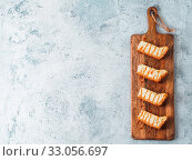 Купить «Caramelized cheesecake slices on wooden cuttingboard. Cheesecake on gray cement background with copy space for text. Top view or flat lay.», фото № 33056697, снято 26 мая 2020 г. (c) easy Fotostock / Фотобанк Лори