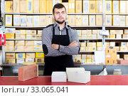 Купить «Man seller showing diverse assortment», фото № 33065041, снято 5 апреля 2017 г. (c) Яков Филимонов / Фотобанк Лори