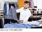 Купить «Young man shopping assistant offering various jacket vv», фото № 33065061, снято 28 сентября 2017 г. (c) Яков Филимонов / Фотобанк Лори