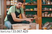 Купить «Pottery - the master is wetting his hands in a bucket of water and continuing to work with clay», видеоролик № 33067429, снято 29 марта 2020 г. (c) Константин Шишкин / Фотобанк Лори