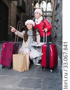 Купить «Cheerful girl and woman with map in scarf», фото № 33067841, снято 19 ноября 2017 г. (c) Яков Филимонов / Фотобанк Лори