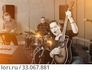 Купить «Attractive female soloist playing guitar and singing with her mu», фото № 33067881, снято 26 октября 2018 г. (c) Яков Филимонов / Фотобанк Лори