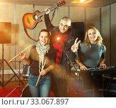 Купить «Three bandmates posing together with musical instruments in rehe», фото № 33067897, снято 26 октября 2018 г. (c) Яков Филимонов / Фотобанк Лори