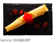 Купить «Roll of thin pancake with red caviar», фото № 33068097, снято 3 апреля 2020 г. (c) Яков Филимонов / Фотобанк Лори