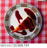 Купить «Slice of delicious classical cheesecake with fruity sauce served in cafeteria», фото № 33068141, снято 6 июля 2020 г. (c) Яков Филимонов / Фотобанк Лори