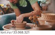 Купить «Pottery - a man in green t-shirt with an iron spatula is helping himself maintaining the shape of a bowl», видеоролик № 33068321, снято 28 мая 2020 г. (c) Константин Шишкин / Фотобанк Лори