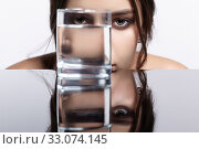 Girl hides her face behind a glass with water. Beauty portrait of young woman at the mirror table. Стоковое фото, фотограф Serg Zastavkin / Фотобанк Лори