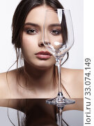 Girl hides her face behind wineglass. Beauty portrait of young woman at the mirror table. Стоковое фото, фотограф Serg Zastavkin / Фотобанк Лори