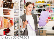 Купить «Interested young woman choosing colorful ribbons and braid for dressmaking in sewing supplies shop», фото № 33074661, снято 18 октября 2019 г. (c) Яков Филимонов / Фотобанк Лори