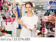 Купить «Portrait of delighted young woman with colorful ribbons for sewing in haberdasher shop», фото № 33074685, снято 18 октября 2019 г. (c) Яков Филимонов / Фотобанк Лори