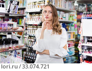 Portrait of young thoughtful and focused woman in cosmetics store. Стоковое фото, фотограф Яков Филимонов / Фотобанк Лори