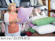 Купить «Adult female buyer choosing colour pillows in the textile store», фото № 33074813, снято 29 ноября 2017 г. (c) Яков Филимонов / Фотобанк Лори