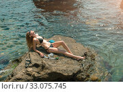 Beautiful slim young woman in a black bikini swimsuit resting on a rocky beach (2016 год). Стоковое фото, фотограф katalinks / Фотобанк Лори