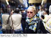 Young woman wearing colorful scarf waiting on the platform of a urban metro station for train to arrive. Public transport. Стоковое фото, фотограф Matej Kastelic / Фотобанк Лори