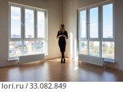 Купить «A girl in a black dress stands between two large windows in a spacious empty apartment», фото № 33082849, снято 3 ноября 2019 г. (c) Иванов Алексей / Фотобанк Лори