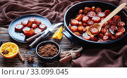 Купить «candied yams, sweet potatoes cooked with cinnamon, orange juice, brown sugar and butter in a black ceramic dish. a portion served on a black plate on a rustic wooden table, horizontal view from above», фото № 33099045, снято 4 октября 2019 г. (c) Oksana Zh / Фотобанк Лори